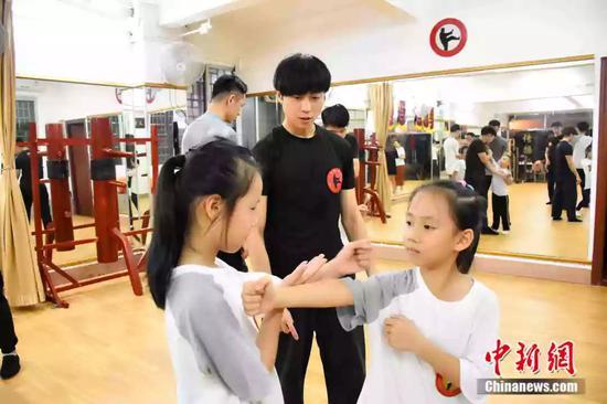 袁师傅的学员3成是女性。图为小女孩在教练的指导下学习咏春拳术。受访者供图