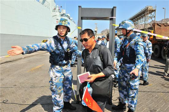 中国海军第十九批护航编队临沂舰抵达也门亚丁港,帮助准备撤离的中国同胞进行安全检查(2015年3月29日摄)。新华社发(熊利兵 摄)