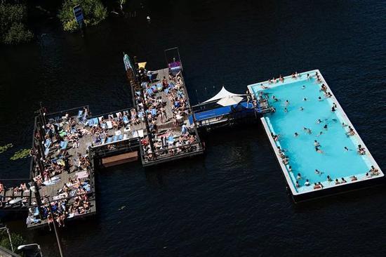 7月26日,在德国柏林,人们在施普雷河上的游泳池中享受清凉。新华社/欧新