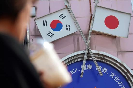 8月2日,在日本首都东京的新大久保,行人从标有日本和韩国国旗的广告牌?#30333;?#36807;。新华社/美联