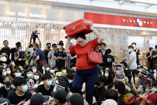 正扛着行李箱穿过非法示威者的女士,以及身后落闸停业的商铺
