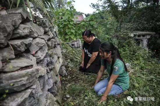 ▲2019年8月15日,湖南慈利县洞溪村,两姐妹来到父亲坟前祭拜,而旁边的房屋就是杀人凶手的家。新京报记者 彭子洋 摄