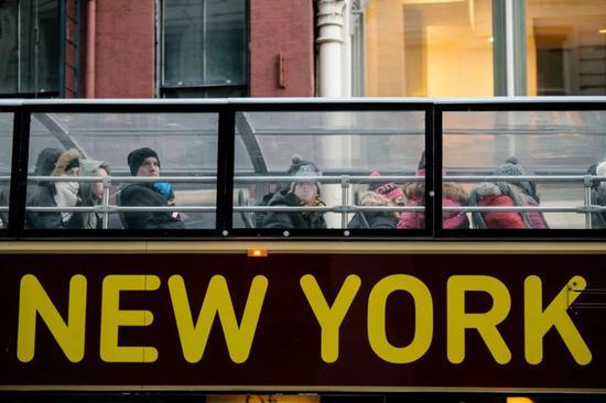2017年12月28日,在美国纽约,游客在观光巴士上游览。新华社/欧新