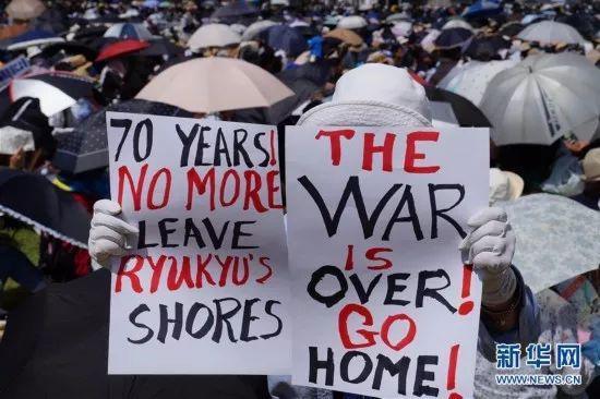 (图为民众手举标语要求美军离开冲绳,驻日美军同样风波不断,美国不得不考虑其影响)