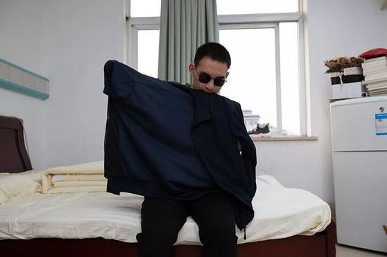 2019年10月24日,重庆西南医院康复楼,清晨,杜富国洗漱完毕后独自穿衣服。新京报记者 李凯祥 摄