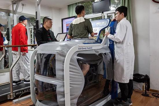 2019年10月24日,杜富国在技师唐鹏的指导下接受反重力跑台训练。新京报记者 李凯祥 摄