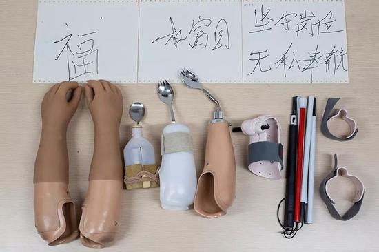 2019年10月24日,重庆西南医院康复楼,杜富国使用的义肢、辅助具及其用辅助具写的字。从左至右:美容义肢、第一代吃饭辅助具、第二代吃饭辅助具、第三代吃饭辅助具、写字辅助具和盲杖辅助具。新京报记者 李凯祥 摄