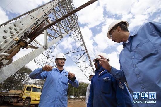 """2018年8月7日,在巴西东南部米纳斯吉拉斯州阿科斯市附近,巴西美丽山特高压输电工程二期第九标段项目中方现场施工管理负责人刘年(左)在施工现场指导巴方员工。美丽山水电站二期项目是中国国家电网公司首个在海外独立投资、建设和运营的特高压直流输电工程,也是""""特高压+清洁能源""""在拉美的示范工程。 新华社记者李明摄"""