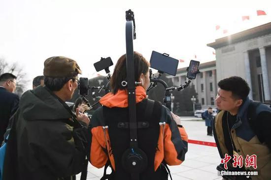 资料图:记者使用多媒体设备进行采访。中新社记者 张娅子 摄