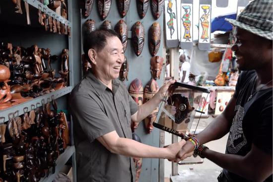 在多哥首都洛美的艺术品市场,谢燕申(左)与一名店主交谈。新华社记者 王腾 摄