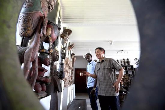 在多哥首都洛美的几内亚湾非洲国际艺术博物馆,谢燕申(右)为一名多哥游客介绍非洲艺术品。新华社记者王腾 摄