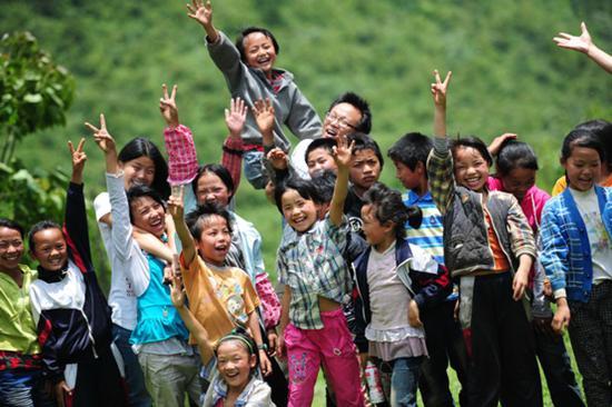 2012年7月,贵州华农大石希望小学,研究生支教团志愿者和孩子们一起。来源:中国文明网