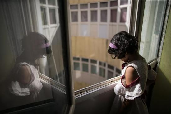 2019年8月28日,在利比亚首都的黎波里一栋废弃楼房中,一名因战乱逃离家园的儿童站在窗边。新华社发(阿姆鲁摄)