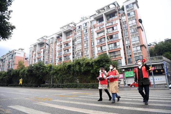 2月1日,重庆市北碚区北温泉街道作孚路社区党委书记王永琴(中)与同事在社区内走访排查。新华社记者 唐奕 摄