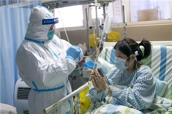 1月24日,在武汉大学中南医院重症隔离病房,中南医院重症医学科主任彭志勇(左)与病情好转的患者黄淑丽互道新春快乐。新华社记者 熊琦 摄