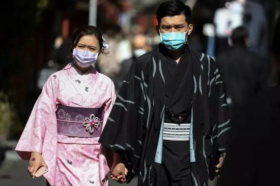 2月18日,在日本东京,两名游客戴着口罩。新华社/路透