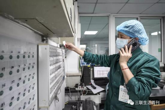 2月14日,醫務人員在金銀潭醫院隔離病房緩沖區呼叫同事。  遠征 攝