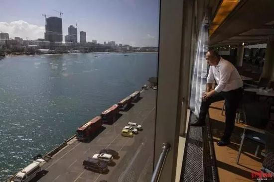 15日,一名船员在船上看着港口。