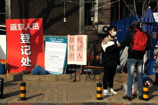 社区做事人员正在向外籍人士讲解防疫仔细事项。
