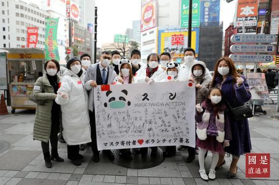 """(资料图)当地时间2月29日,一个由旅日侨胞发起的公益行动团体——""""口罩熊猫""""在东京池袋为日本民众免费发放口罩。中新社发 钟欣 摄"""