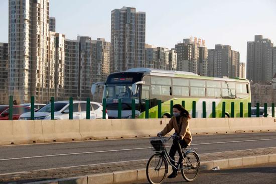 013县道,一位女士骑自走车进京。