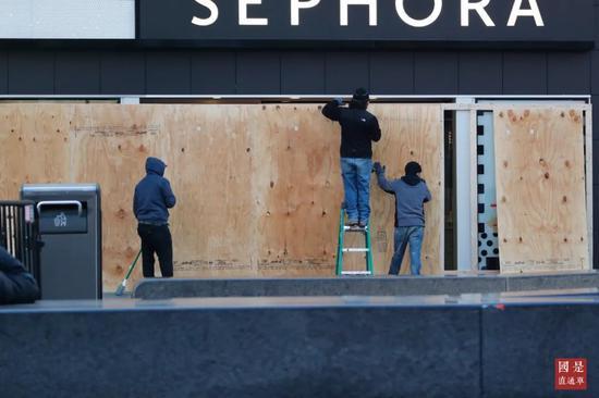 当地时间3月21日,美国纽约时代广场一个已经停业的商家,工作人员用木板封闭大门。中新社记者 廖攀 摄