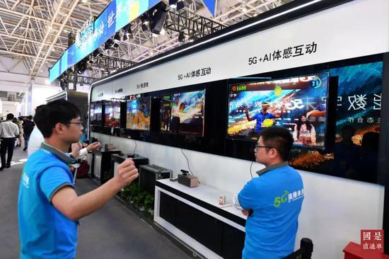 (资料图)中国移动展台的工作人员在演示5G应用。中新社记者 吕明 摄