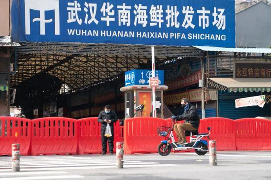1月29日,市民经过已经被封闭的武汉华南海鲜批发市场