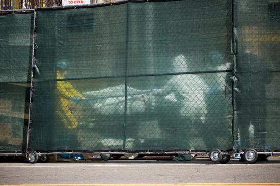 4月6日,在美国纽约一家医院外,医护人员运送物化亡患者遗体。新华社发 (郭克摄)