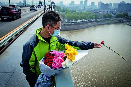为外达全国各族人民对抗击新冠肺热疫情搏斗捐躯烈士和去逝同胞的深刻哀悼,4月4日10时首,全国人民默悲3分钟,汽车、火车、舰船鸣笛,防空警报鸣响。别名市民在武汉长江大桥上去长江中抛洒鲜花,以示哀悼。图/IC