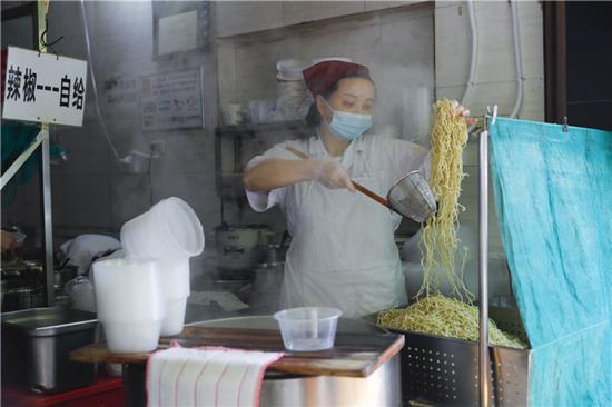 """4月22日,在武汉市粮道街的家阳""""赵师傅""""天天红油热干面店,厨师制作热干面。新华社记者 沈伯韩 摄"""