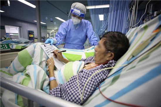 4月20日,在武汉大学中南医院ICU,患者刘先生在病床上写感谢信。新华社发(李晗 摄)