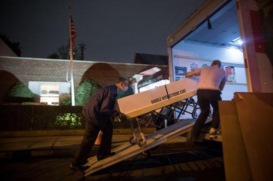 4月29日,在美国纽约昆斯区,殡仪馆工作人员将装有遗体的纸箱搬上车准备运到外地处理。新华社发(郭克摄)