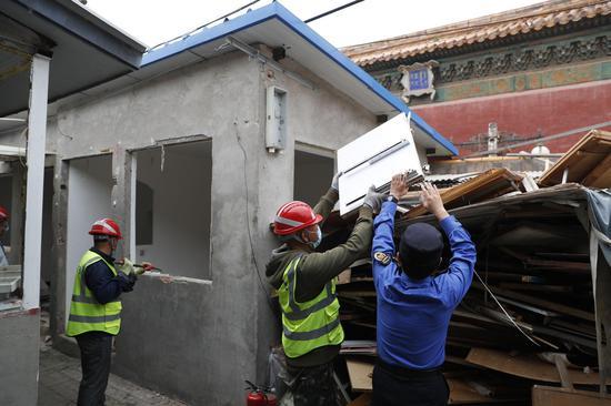 城管执法队队员与工人一首清算修建垃圾。摄影/新京报记者 侯少卿