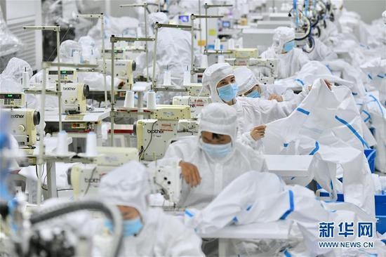 在福建晋江,工人在生产防护服(2月4日摄)。 新华社记者 姜克红 摄