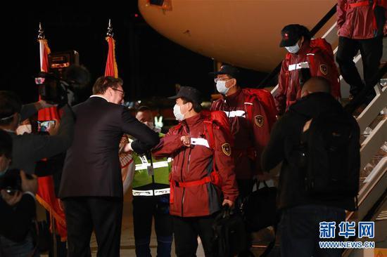 """3月21日,在塞尔维亚首都贝尔格莱德,前来迎接的塞尔维亚总统武契奇(左)与中国援助塞尔维亚抗疫医疗专家组成员""""碰肘""""致意。中国援助塞尔维亚抗疫医疗专家组一行6人21日晚乘专机抵达贝尔格莱德。 新华社记者 石中玉 摄"""