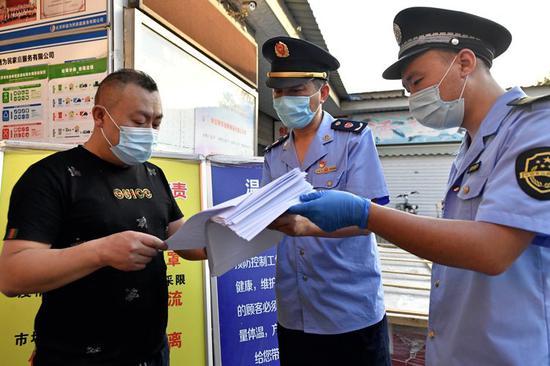 6月16日晚,特吉特菜市场,东城市场监管局执法人员向商户发放北京市新型冠状病毒肺炎疫情消毒指引。