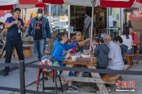 当地时间6月19日,美国加州圣马特奥县居民在一家餐厅就餐。目前,加州重启经济进入第三阶段,只要所在县允许,电影院、餐厅等高风险设施可以重新营业。中新社记者 刘关关 摄