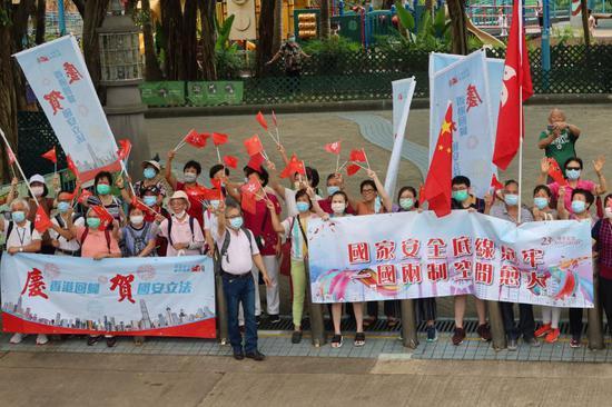 图为:沿途市民手持红旗夹道迎接
