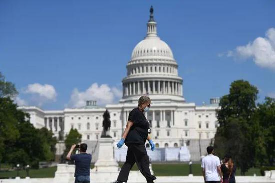 ▲资料图片:5月15日,在美国首都华盛顿,戴口罩的行人从国会大厦附近走过。新华社记者 刘杰 摄