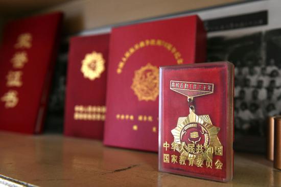 """国家教委为张守中颁发的""""高校后勤做事三十年""""奖章。"""