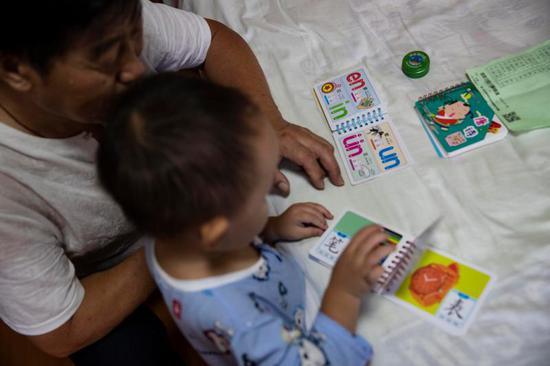 郭希宽在教小楷读生字卡片,对孙子甚是宠溺。