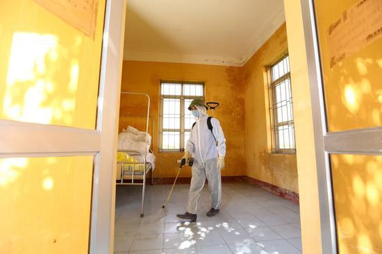 当地时间7月30日,防疫人员在越南首都河内一处隔离设施喷洒消毒剂。 新华社 图