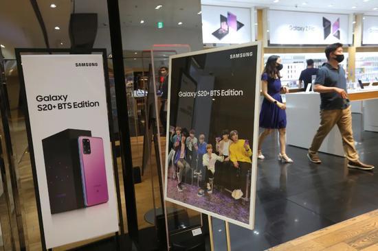 7月7日,人们走过位于韩国首尔的一家三星品牌专卖店前放置的广告牌。新华社/美联