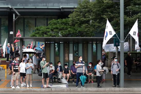 8月15日,在韩国首尔,戴口罩的人们在公交站等车。新华社/美联