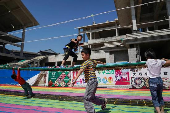 顺德广场外,一侧是烂尾的楼盘,一侧是嬉戏的儿童