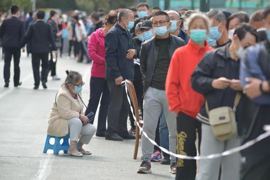 (2020年10月12日,山东省青岛市全员核酸检测进入第二天,居民在一处社区内有序进行核酸检测。)
