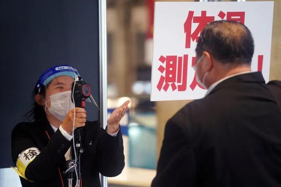 10月28日,在日本东京附近的千叶县,一名展览工作人员为一名男子进行体温检测。新华社/美联