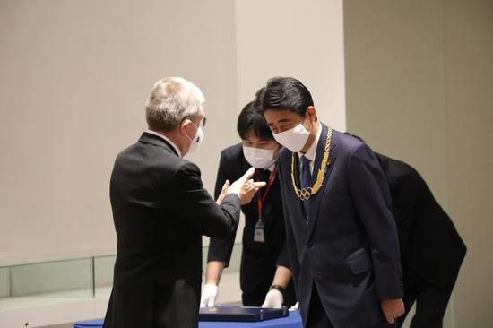被付与勋章时,安倍鞠躬致谢。