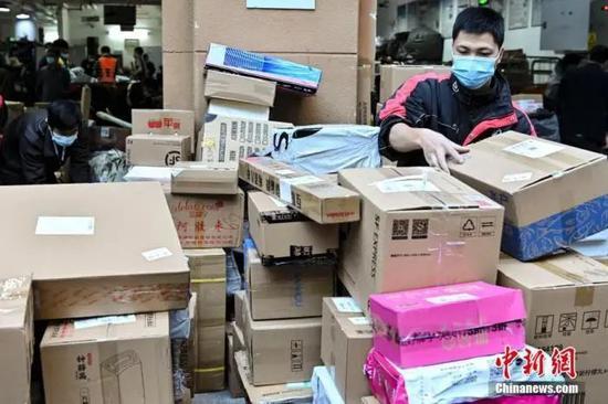 资料图:11月12日,广东省广州市,一名快递员在快递网点整理将要派送的快件。中新社记者 陈骥旻 摄